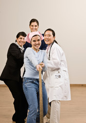Housewife, doctor and businesswomen pulling rope in tug-of-war