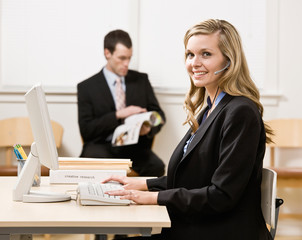 Businesswoman talking on headset with co-worker in background