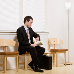 Businessman anxiously waiting for appointment in waiting area