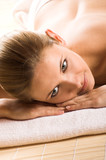 beautiful woman in spa is relaxing on a towel poster
