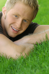 young blond male smiling while on grass