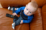Little baby boy playing with TV remote - 9710361