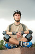 Boy on rollerblades sits with crossed legs yoga pose
