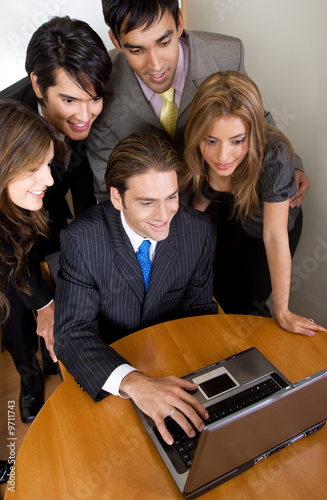 business team browsing on a laptop in their office