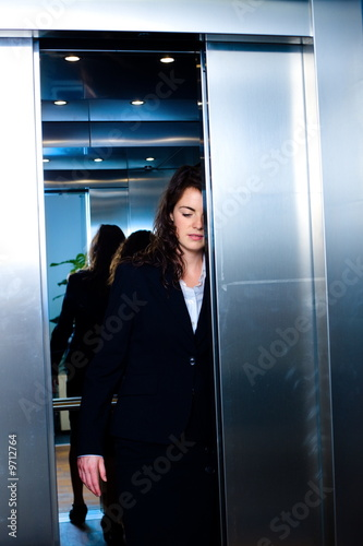 Young businesswomen leaving the office, using elevator.