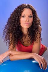 Portrait of a pretty curls hair women on blue pilates ball