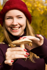 happy smiling blond girl showing a mushroom