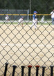 baseball bats learning against dugout fence as game is played