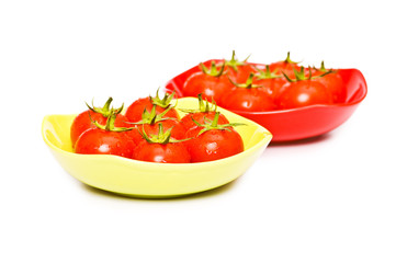 Wet whole tomatos arranged isolated on white.
