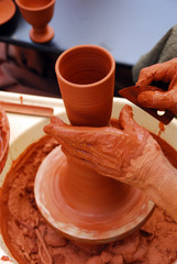 View of the hands of a potter working on a cup