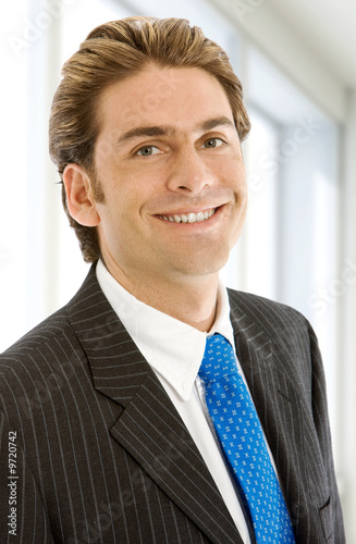 Friendly business man portrait - smiling in his office.
