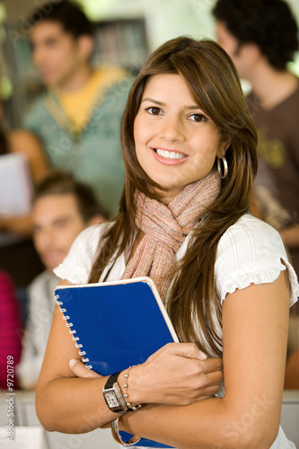 Beautiful girl holding notebooks - smiling in the classroom