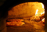 Pizzas baking in an open firewood oven poster