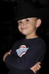 Little boy wearing a cowboy hat and a baseball shirt