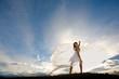 Frau in weiß steht vor untergehender Sonne