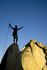 A rock climber celebrates on the summit of a rock spire.