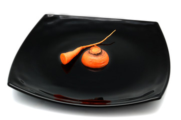 irony healthy diet concept - bit of carrot on black plate