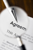 Magnifying glass over agreement paperwork and pen. poster