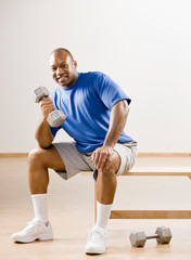 Determined man working out with dumbbells in health club