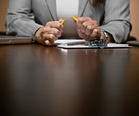 Frustrated businesswoman working late at desk breaking pencil