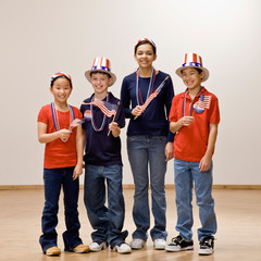 Patriotic children holding American flag and wearing hats