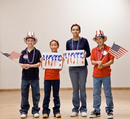 Patriotic children wearing hats with vote sign