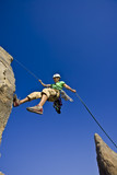 Rock climber rappelling from the summit of a rock spire. poster