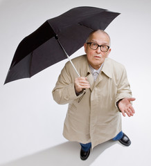 Curious man in raincoat holding umbrella checking for rain