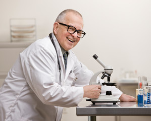 Research scientist in lab coat with microscope in laboratory