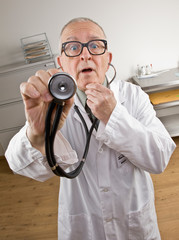 Doctor in lab coat using stethoscope during checkup