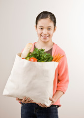 Girl holding grocery bag full of fresh wholesome fruits