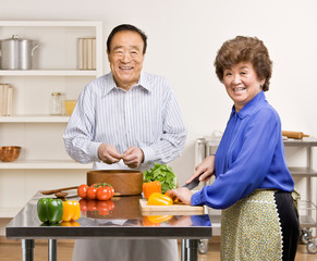 Man preparing wholesome salad with wife in kitchen for dinner