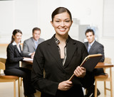 Confident businesswoman with notebook and co-workers