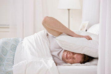 Man using pillow to block out noise while trying to sleep