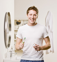 Man in pajamas in bathroom holding toothbrush and toothpaste