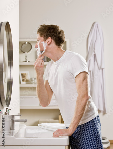 Man in pajamas in bathroom using shaving foam and shaving