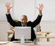 Excited businessman sitting at desk cheering