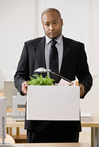 Businessman sadly packing personal desk items in box