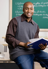 Teacher sitting on desk with text book in school classroom
