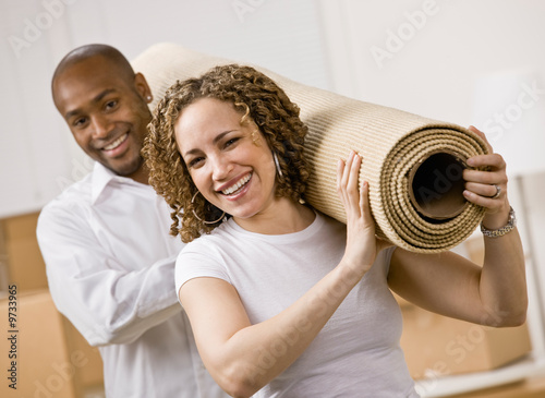Happy couple moving into new home carrying rug