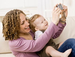 Mother taking self-portrait of herself and son with camera