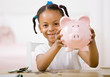 Girl putting money into piggy bank for future savings
