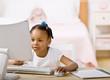 Determined girl doing homework on computer in bedroom