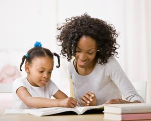 Mother helping daughter do homework in workbook