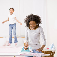 Housewife ironing laundry while girl jumps on bed