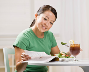 Happy woman eating healthy lunch while reading magazine