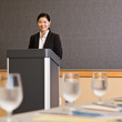Businesswoman standing behind podium