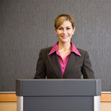 Businesswoman standing behind podium