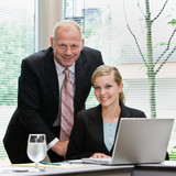 Businessman and female co-workers posing with laptop