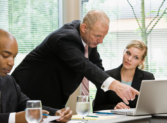 Businessman pointing to female co-workers laptop